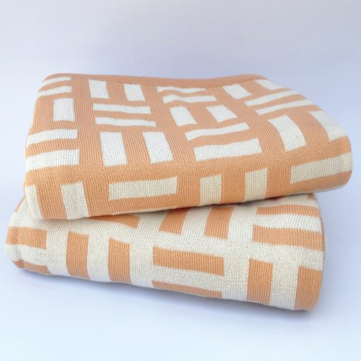 two Bricks designed Branberry cotton blankets in Orange and White, folded and stacked on each other.