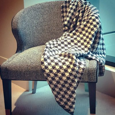 Branberry Pure Australian Merino Wool Houndstooth Cot Blanket draped over an arm chair