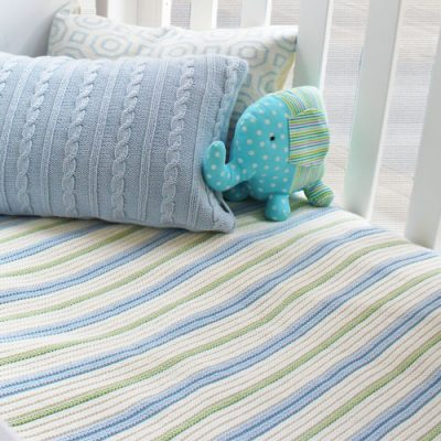 Branberry Striped Garter knitted baby blanket in blue mint and white, displayed on a cot