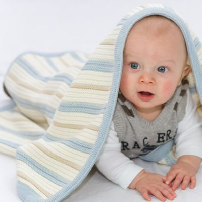 Baby boy laying with his Branberry Striped garter knitted baby blanket in blue, pebble & white.