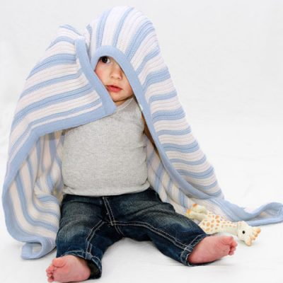 Toddler playing with a Branberry Striped Garter knitted baby Blanket in Blue & Ivory White