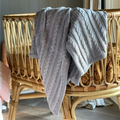 Branberry, Australian made cotton and wool blend cable cot blanket draped over the edge of a bassinet