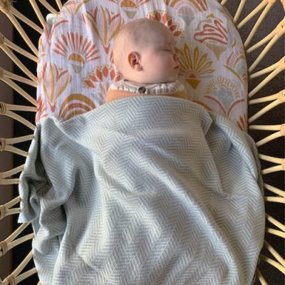 Baby sleeping wrapped in a Branberry Grey and white, cotton & wool blend Herringbone blanket.