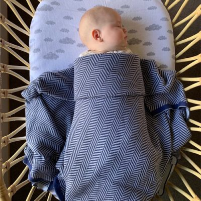 Baby sleeping wrapped in a Branberry navy and grey, cotton & wool blend Herringbone blanket.