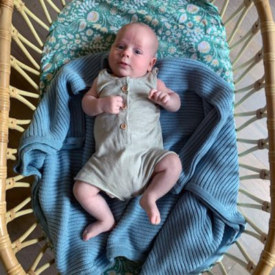 Ariel view of a baby laying on an Australian Made, Branberry Garter Blanket in Stone blue in his bassinet.