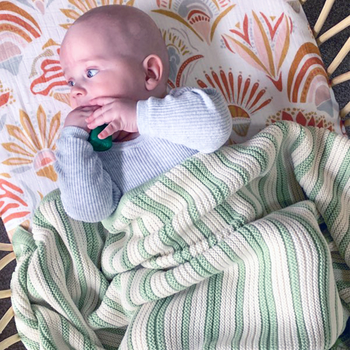 Smiling Baby wrapped in a Branberry Australian Made, Cotton & Wool Blend Striped Blanket in Mint and Ivory White