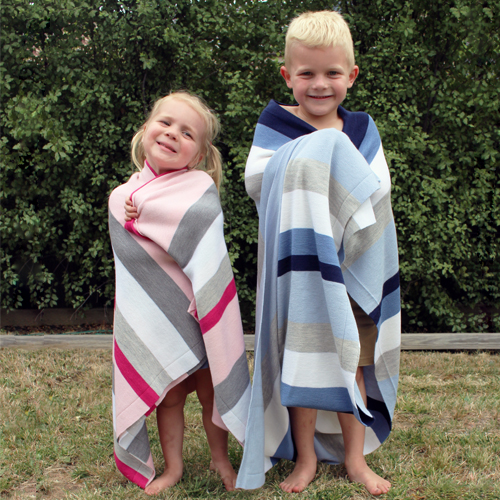 a boy wrapped in a pure wool blue striped blanket and a girl wrapped in a pink striped pure wool blanket