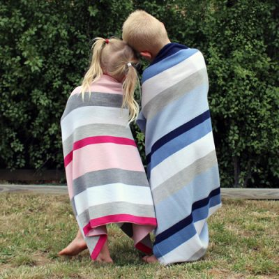 Two children standing wrapped in a bright striped Branberry Fusion Blankets. The girls iblanket is pink and grey stripes and the boys is blue and white stripes. Made in Australia using merino wool
