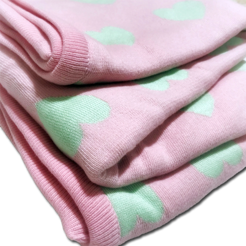 a folded Branberry pure cotton love heart blanket in pink and mint
