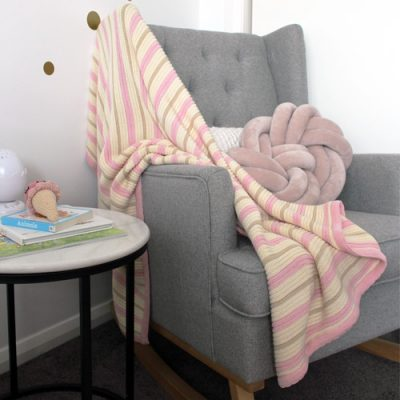 Branberry Striped garter knitted baby blanket in pink, pebble & white, displayed on an arm chair in the nursery