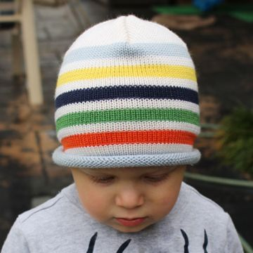 Toddler boy wearing a Bright and vibrant coloured striped pure wool rainbow Branberry beanie