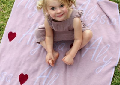 Girls sitting on a personalised merino wool branberry blanket in pink with love hearts
