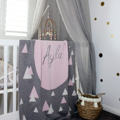 personalised pure merino wool name blanket draped over the edge of a cot