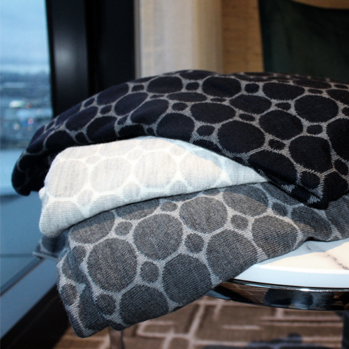 A Stack of folded merino wool, dots and spots knitted blanket design, navy, grey and white