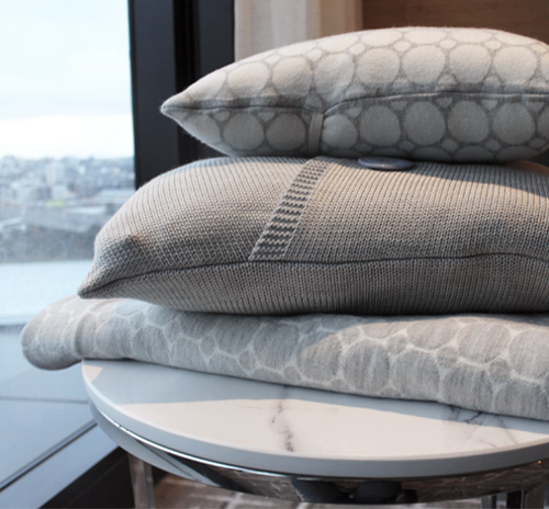 A matching stack of merino wool knitted blanket and cushions in white and light grey