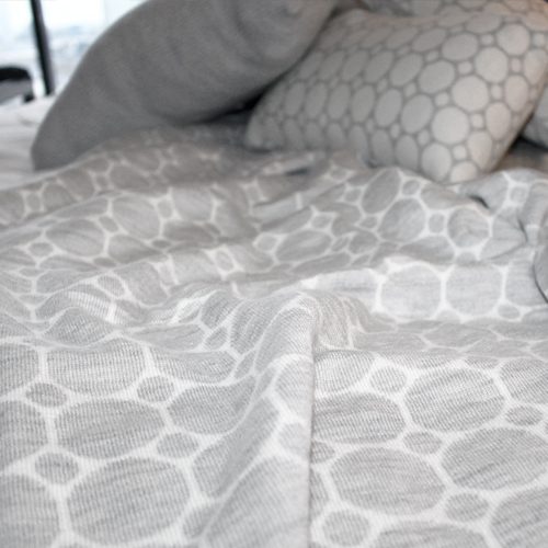 merino wool knitted throw blanket with a dots and spots design in white and light grey