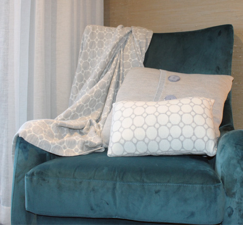 merino wool, dots and spots knitted throw blanket design in white and light grey draped on an armchair with cushions