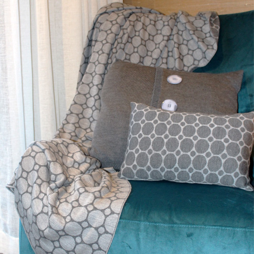 Dots and Spots design, knitted merino wool throw blanket in grey draped on a couch with cushions
