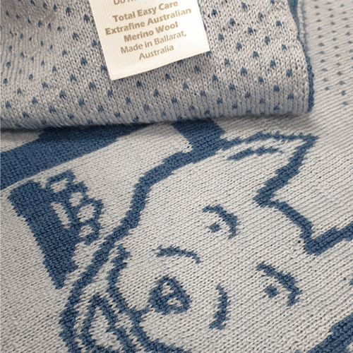 Farm animal merino wool bluer blanket. Close up of knitted sheep dog and care label