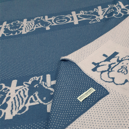 A blue spotted merino wool blanket that has Farm animals peeking through a fence