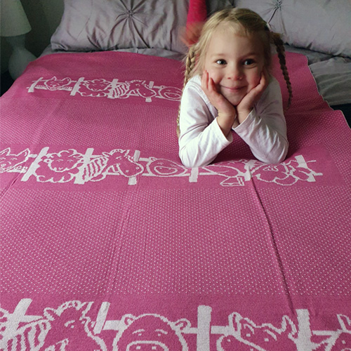 Little girl laying on her Branberry pure merino wool Farm ANimals knitted blanket in pink
