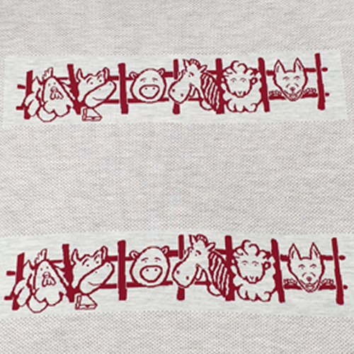Australian made knitted merino wool Farm animals blanket in red. Showing two rows of farm animals peeking through the fence.
