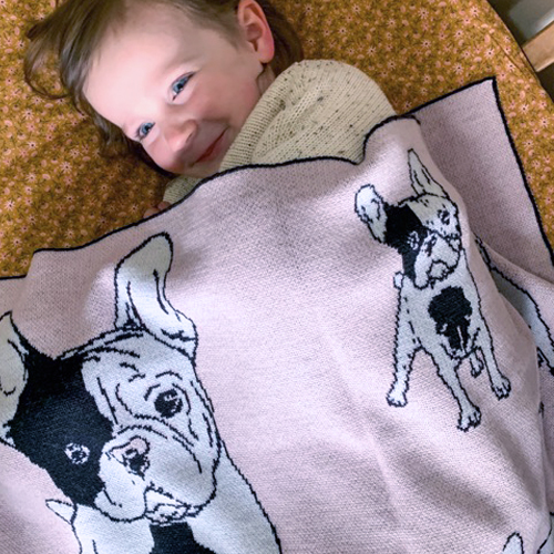 Toddler Girl Smiling while wrapped in a Branberry, Pure Wool French bulldog designed blanket in Pink
