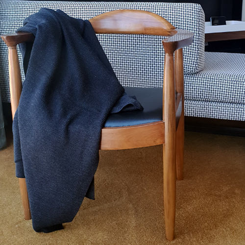A Branberry Charcoal Pure Merino Wool Throw blanket draped over a wooden chair.