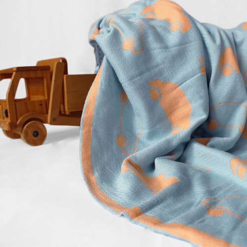 wooden truck with a branberry pure cotton cars blanket in blue and orange hanging out of it