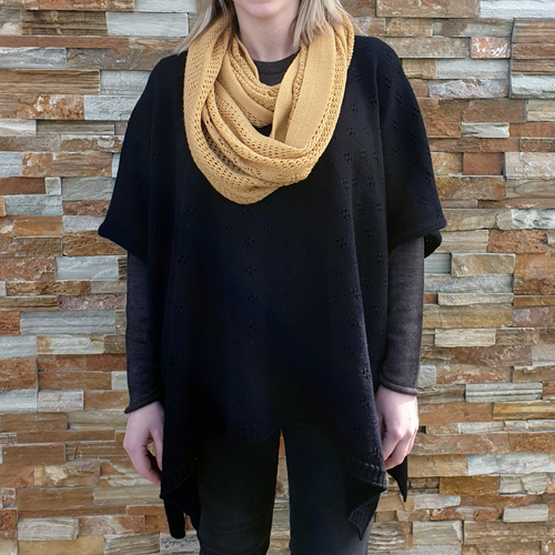 lady standing wearing a branberry Pure Merino Wool Poncho in Black paired with a pure wool Branberry vintage loop scarf in mustard