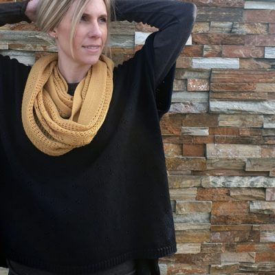 lady with her hand on her head wearing a Branberry merino wool poncho in black paired with a branberry pure wool vintage loop scarf in mustard