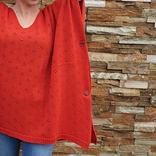 close up of a the button sides of a lady wearing a made in Ballarat, Branberry pure merino wool knitted poncho in coral