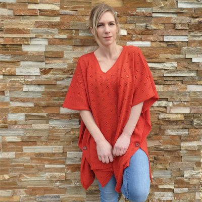 lady standing and leaning against a wall wearing a branberry Pure Merino Wool Poncho in Coral
