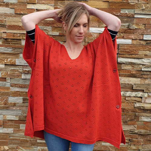 a lady with her hands up on her head wearing a branberry Pure Merino Wool Poncho in coral