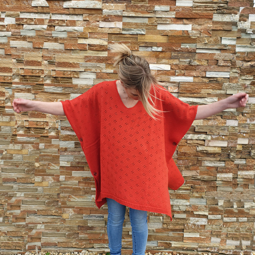 lady with her arms out, wearing a branberry Pure Merino Wool Poncho in coral