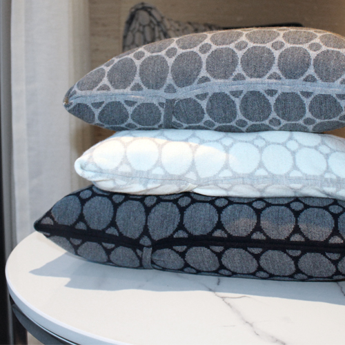 Pure Australian Merino Wool knitted Branberry Cushions in a spot and dot design. Navy, Grey and White cushions are all stacked on top of one another