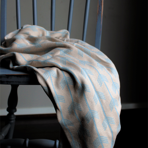 Australian made Branberry pure cotton cot blanket. Blue and beige arrows design hanging over a chair