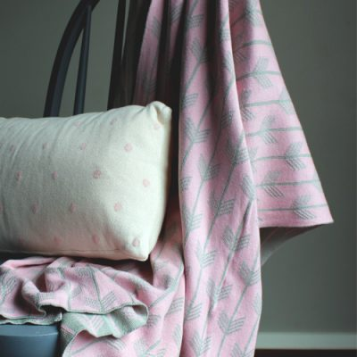 Australian made Branberry pure cotton cot blanket. Pink and grey arrows design hanging over a chair with a cushion