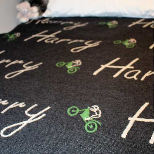 Branberry personalised pure merino wool name blanket in dark grey with green dirt bikes spread on a bed with cushions