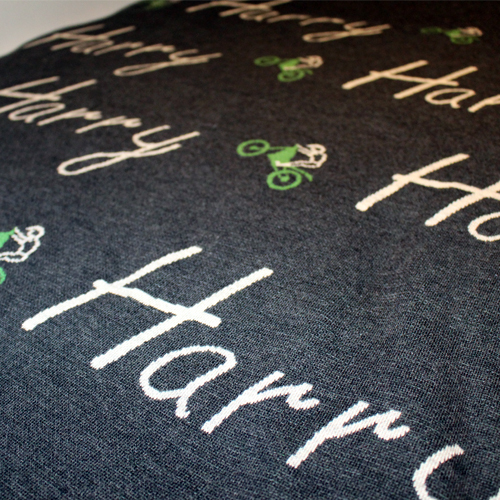 Branberry personalised pure merino wool name blanket in dark grey with green dirt bikes spread on a bed