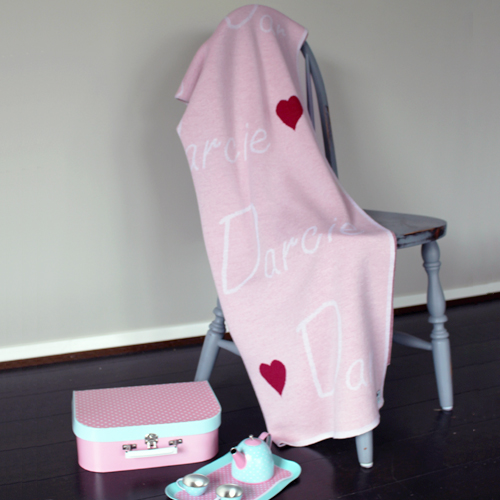 Branberry personalised pure merino wool name blanket in light pink hanging on a chair