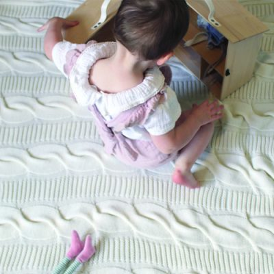 A girl playing on a Branberry chunky knitted pure wool cable blanket