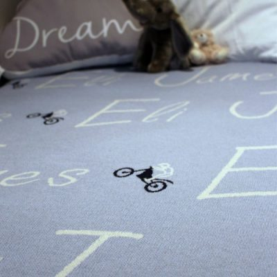 Personalised Dirt Bike Blanket. A Blue. Pure Merino wool Branberry blanket set up on a bed