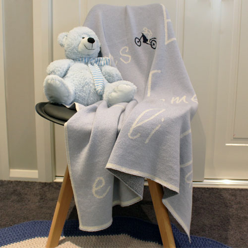 Personalised Branberry Pure merino wool blanket that's draped over a chair with a teddy