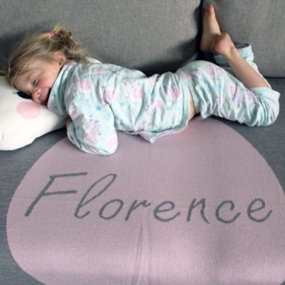 girl laying on a personalised pure merino wool knitted Branberry blankets in pink, grey & white