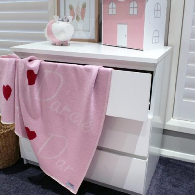 Branberry personalised pure merino wool name blanket in light pink hanging out of a chest of draws