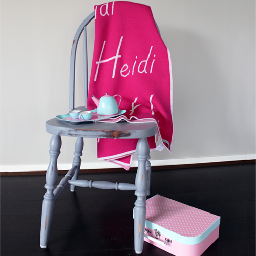 Personalised Branberry, Bright pink Pure merino wool blanket that's draped over a chair with a tea set