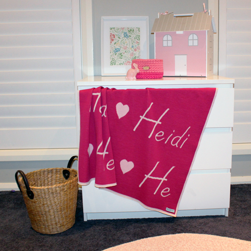 Branberry personalised pure merino wool name blanket in brightpink hanging out of a chest of draws
