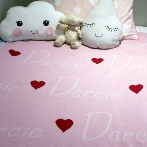 Branberry personalised pure merino wool name blanket in light pink spread on a bed with cushions