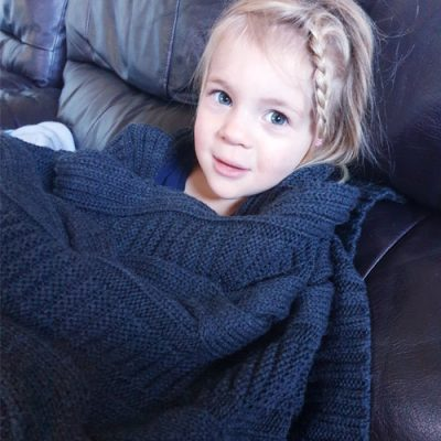 Alittle girl sitting on the couch snuggly wrapped in a Branberry Chunky Cable, merino wool blanket